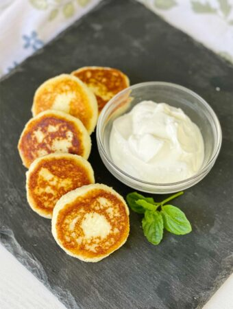 Cheese Pancakes on the display board with a bowl of sour cream
