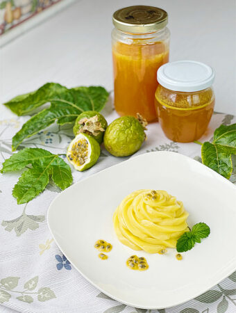 Jars with passion fruit juice, passion fruit simple syrup and a plate with passion fruit curd