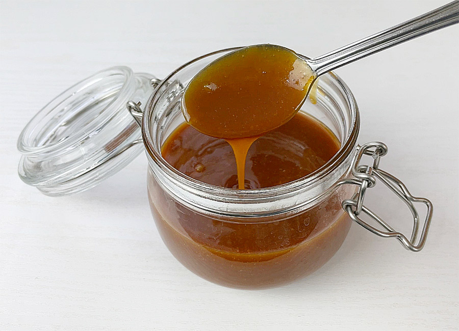 Runny caramel dripping from a spoon